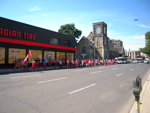 Students pulling the bus downtown past a Canadian Tire.