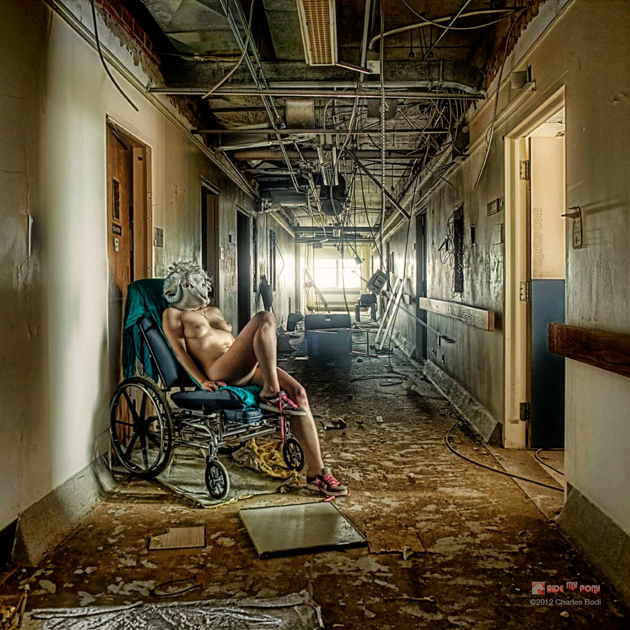photo de charles bodi representant une femme nue avec un masque de chevre dans un couloir d'hopital désaffecté