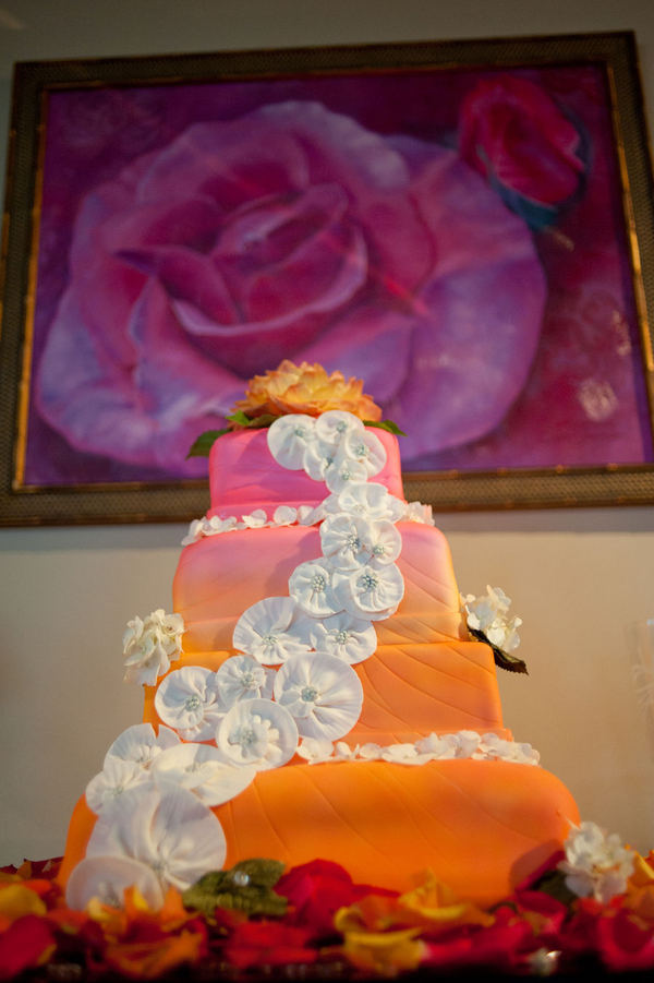 Stunning four tier square wedding cake with an orange to pink gradient and