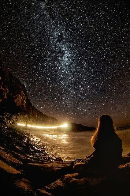 Girl sitting by the ocean at night, looking up to the stars and the universe