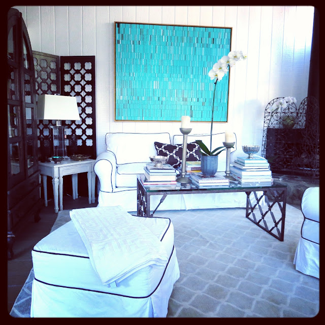 Turquoise piece by Brian Wills in Coco of COCOCOZY's living room with a white sofa and matching armchair and ottoman with brown piping and a COCOCOZY Fence rug