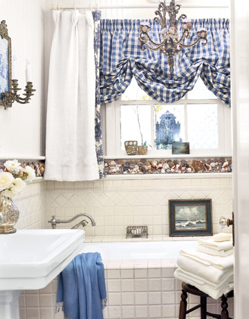 Stunning Focal point in this beach bathroom unmistakably the wall mounted resin clam shell over the Bathtub The shades of the mosaic glass tile matches the
