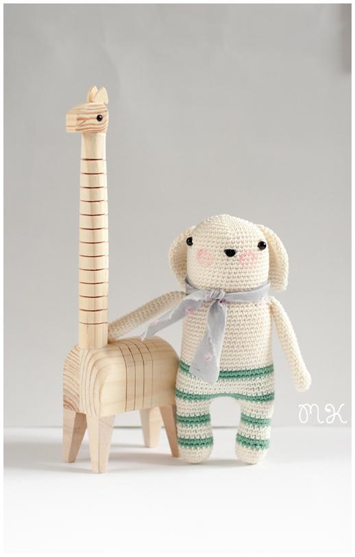 muñeco amigurumi hecho a ganchillo y jirafa de madera