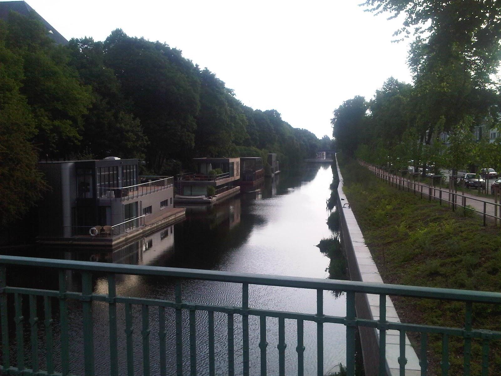 Eilbekkanal am Morgen mit Hausbooten, ruhiges Wasser, Bäume, Spiegelung auf dem Wasser, grünes Ufer.