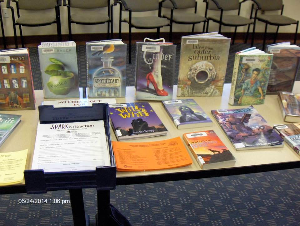 "Table top book display with ""Spark a Reaction"" teens' summer reading book review forms. Among visible titles: Hold Fast by Blue Balliet, Peeled by Joan Bauer, The Apothecary by Maile Meloy, Cinder by Marissa Meyer, Tales From Outer Suburbia by Shaun Tan, Will & Whit by Laura Lee Gulledge, Atomic Robo and the Fightin' Scientists of Tesladyne by Brian Clevinger."