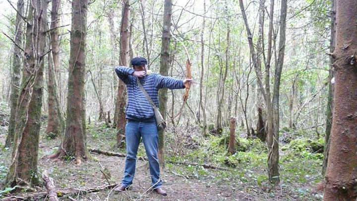 A man in a forest taking aim with a recurve bow