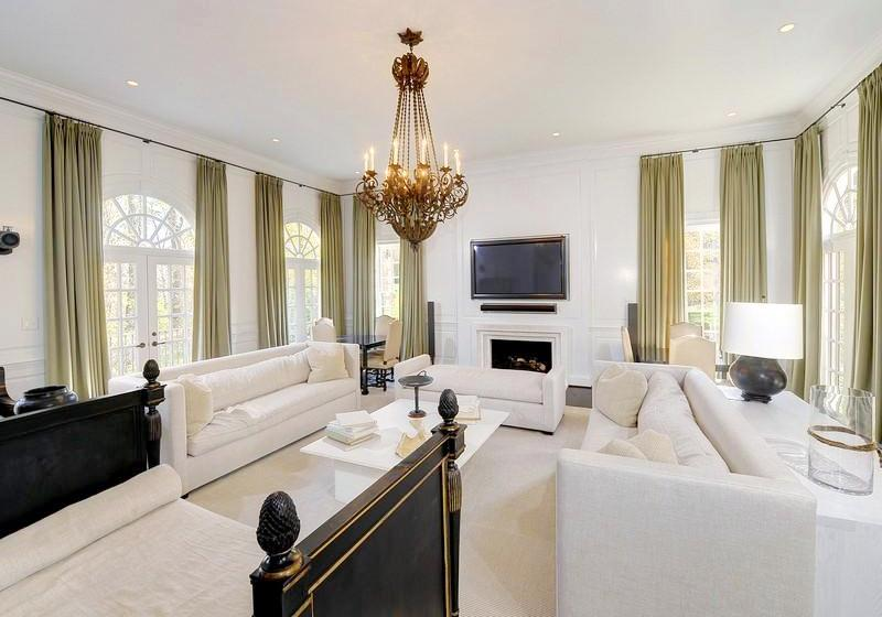 The Bright And Cheerful Family Room Or Den Has A Wall Mounted Television Dueling White Sofas And Lots Of Khaki Drapes Above