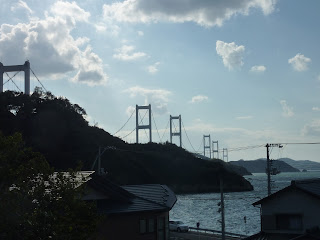 The Kurushima-Kaikyo bridge stretching into the distance as seen Oshima island on the Shimanami Kaido. Houses in the foreground