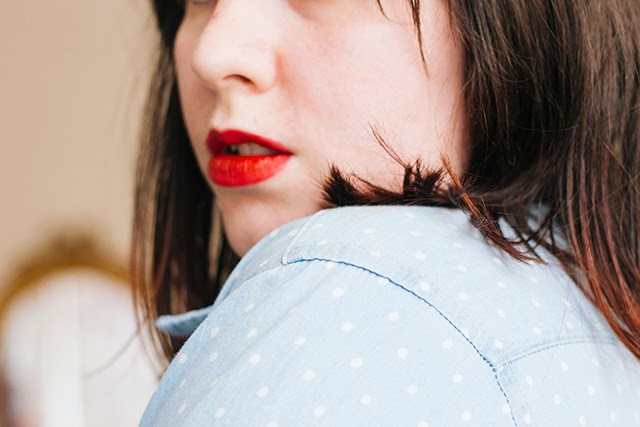 over the shoulder with red lipstick and polka dot denim blouse