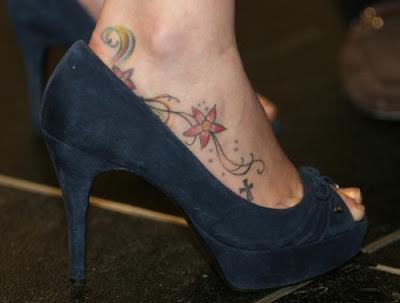 Mulher de salto e tatuagem no pé