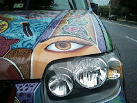 headlight of car with eye painted above it and other bright colors around lamp