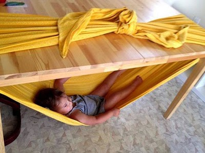Tie a blanket around a table for a kid-sized hammock. Make sure to tie it tight!