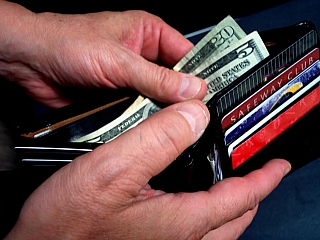 A man removing money out of a wallet