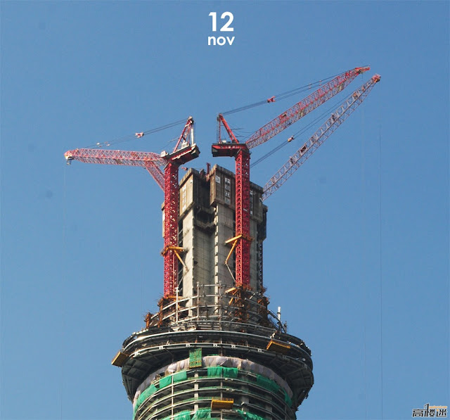 Photo of four red tower craned building the central core