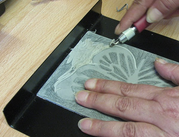 Lino block being cut on a bench hook
