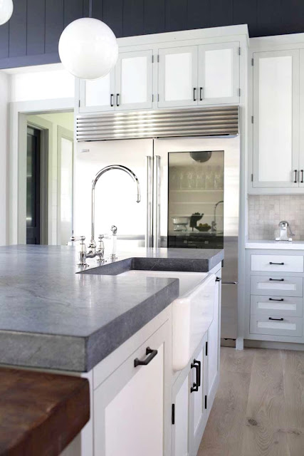 Kitchen island with grey soapstone counters and white cabinets
