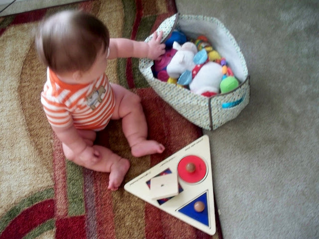 seven month old boy plays with puzzle and toys