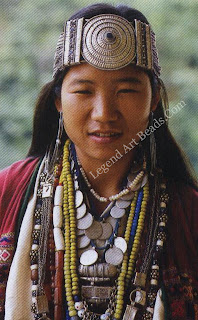 Young maiden of the Aka tribe wears a profusion of glass bead, stone and silver necklaces, from one of which hangs the ga'u or charm box. Her forehead is encircled by the lenchhi, a band made distinctive by the large silver disc in the centre ornamented in repousse.