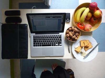 Bananen, Äpfel, Pfirsiche, Nüsse, Zwieback, Ziegenkäse neben Recher, Handy, Notizbuch usw.