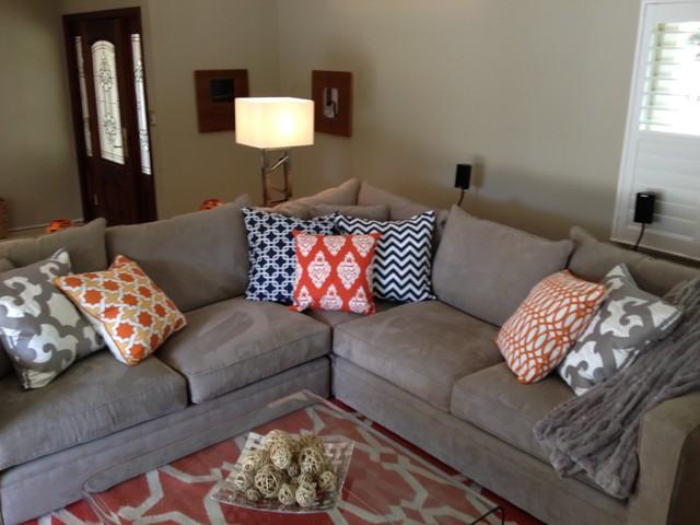 Sala moderna decorada con gris como color principal y acentos naranjas