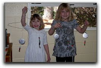 two children hold mobiles they made in church school