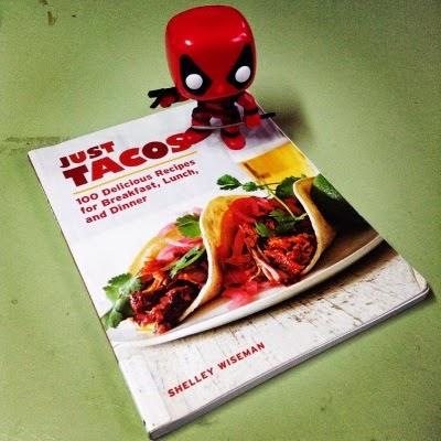 Tiny Deadpool perches on the corner of a trade paperback copy of Just Tacos. Its cover features two soft tacos stuffed with meat and topped with cilantro. Book and figure rest on a scarred, pale green surface.