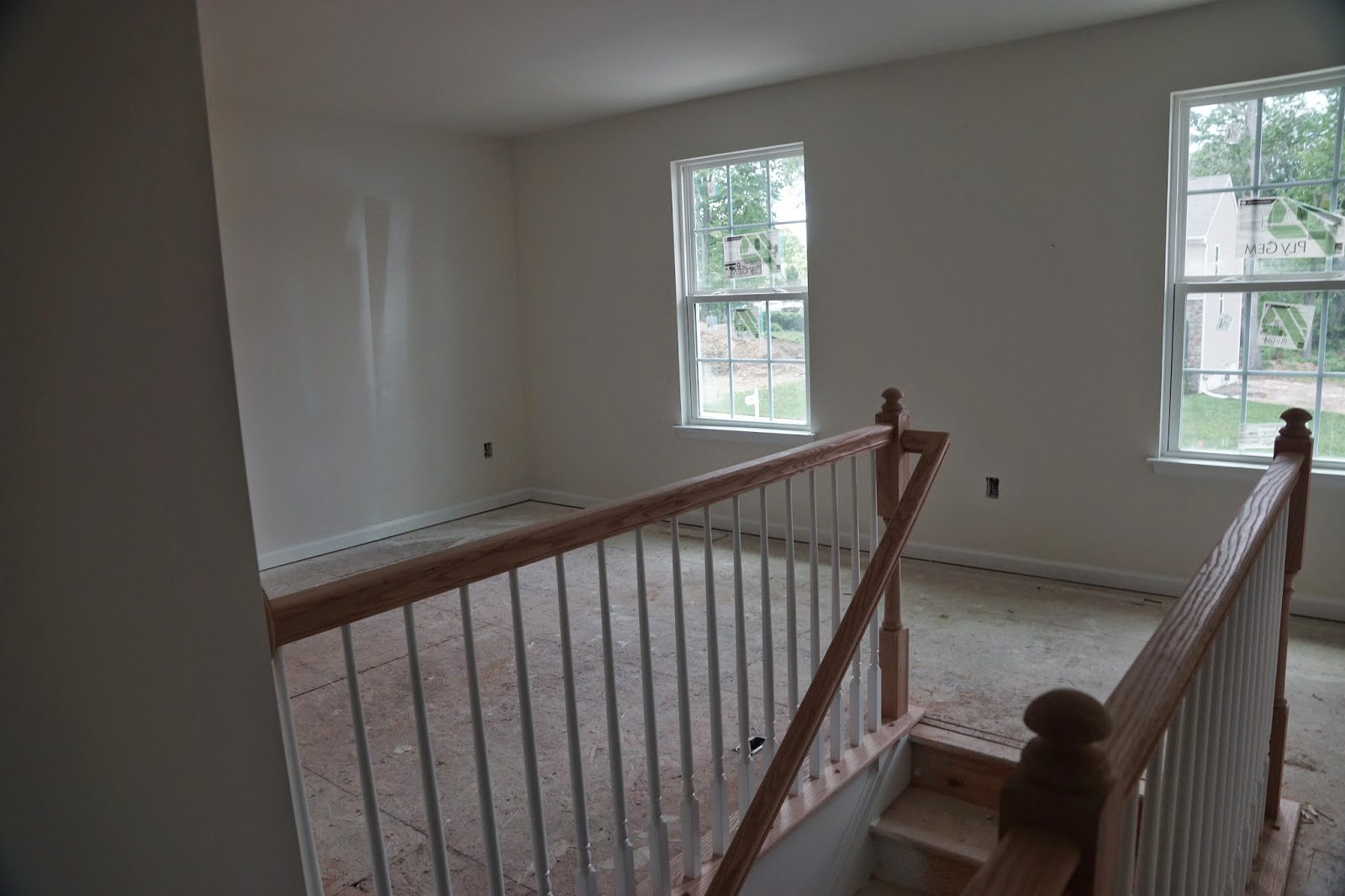 Picture of the unfinished banister on the top of the stairs as viewed from the middle of the hallway