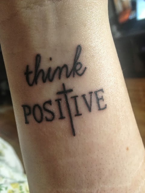 Think positive writing tattoo on wrist