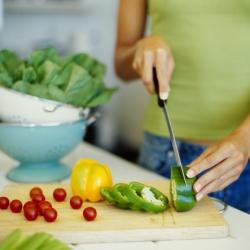 personne en train de préparer la cuisine et de couper des légumes