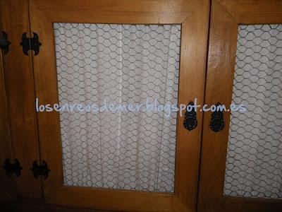 Puertas de un mueble rústico, decoradas con visillos y tela de gallinero