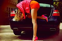 Rosie Huntington Whiteley leggy in short orange shorts getting into the car trunk