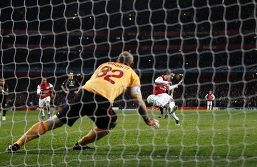 Arsenal forward Robin van Persie scores from the penalty spot against AC Milan