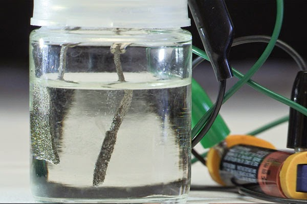 Stanford scientists have developed a low-cost device that uses an ordinary AAA battery to split water into oxygen and hydrogen gas. Gas bubbles are produced by electrodes made of inexpensive nickel and iron. (Credit: news.stanford.edu) Click to enlarge.