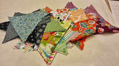colorful fabrics cut in tirangles ready to be sewn together