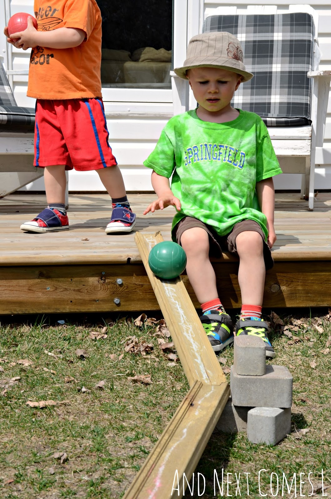 J playing with DIY outdoor ball run made from loose parts in the backyard from And Next Comes L