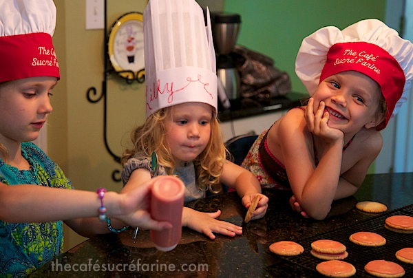 Girls frosting Strawberry Glazed Butter Thins in The Café kitchen.