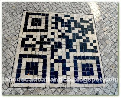 Imagem de um QR code incrustado em pedras portuguesas no chão da Rua Garret, Chiado, Lisboa.