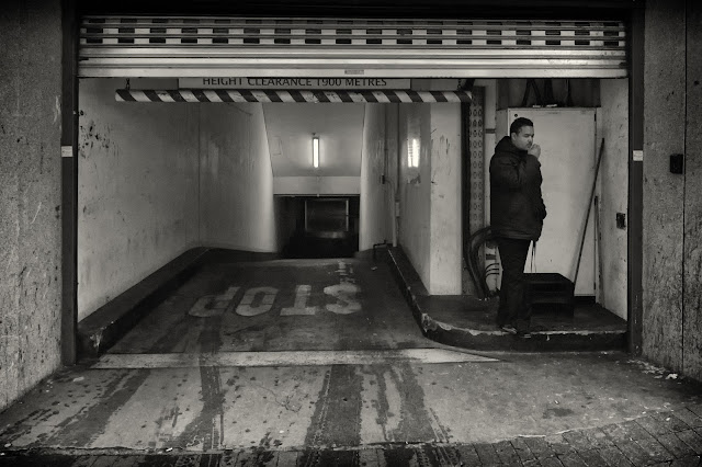 A street photo of a man at the entrance to an underground car park on St George's Mall Cape Town