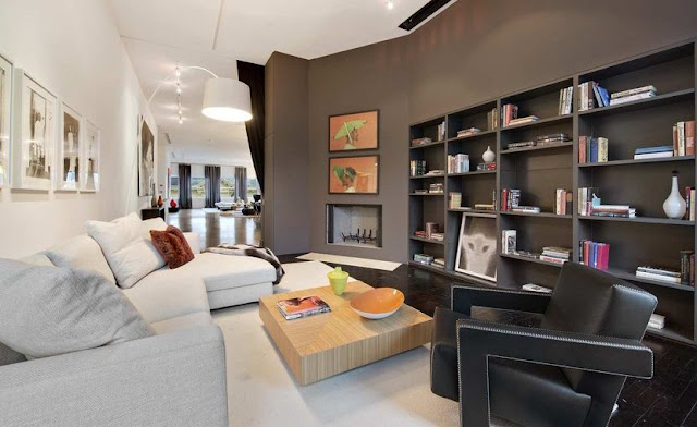 Den in a Soho Condo in New York with white sofas, a low wooden table, gray wall bookcase and fireplace