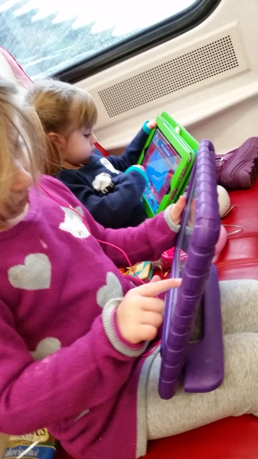 4 year old and 2 year old on train with ipads