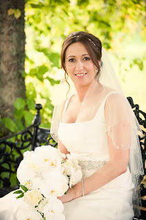 bride with her hair in a textured bun with soft volume, a jenny packham headband, and holding a bouquet