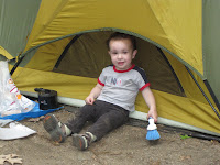 Toddler leaning on a tent