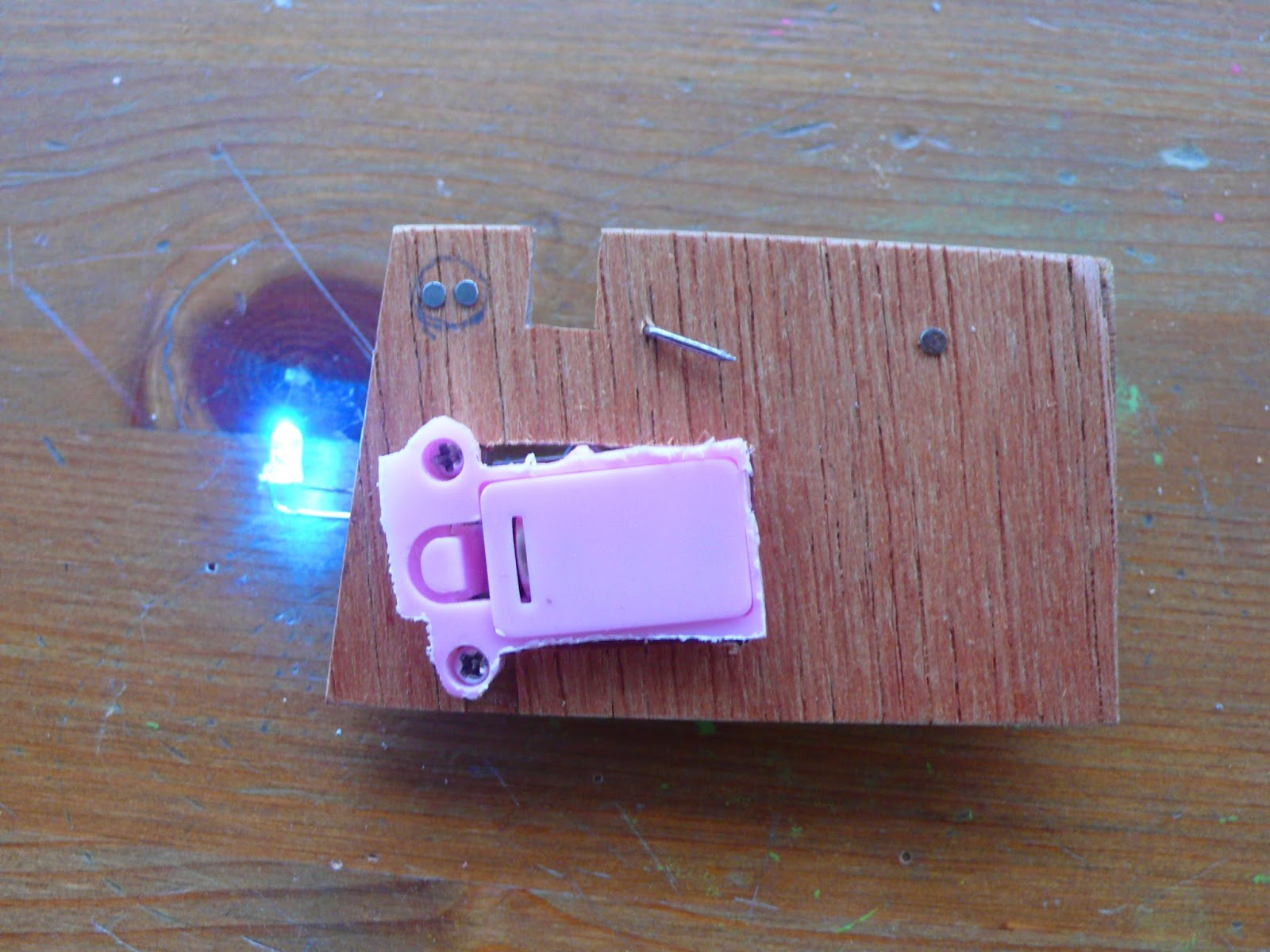 The front of a prototype circuit brooch, with an illuminated LED.