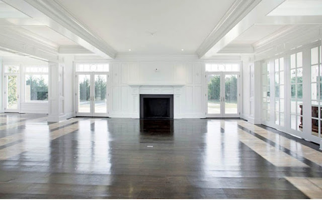 enormous living room with wrap around french doors and windows and a fireplaces