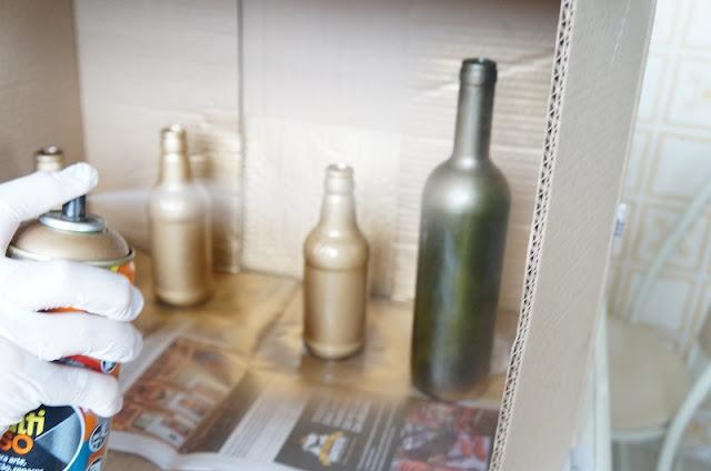 aplicando tinta dourada na garrafa de vinho