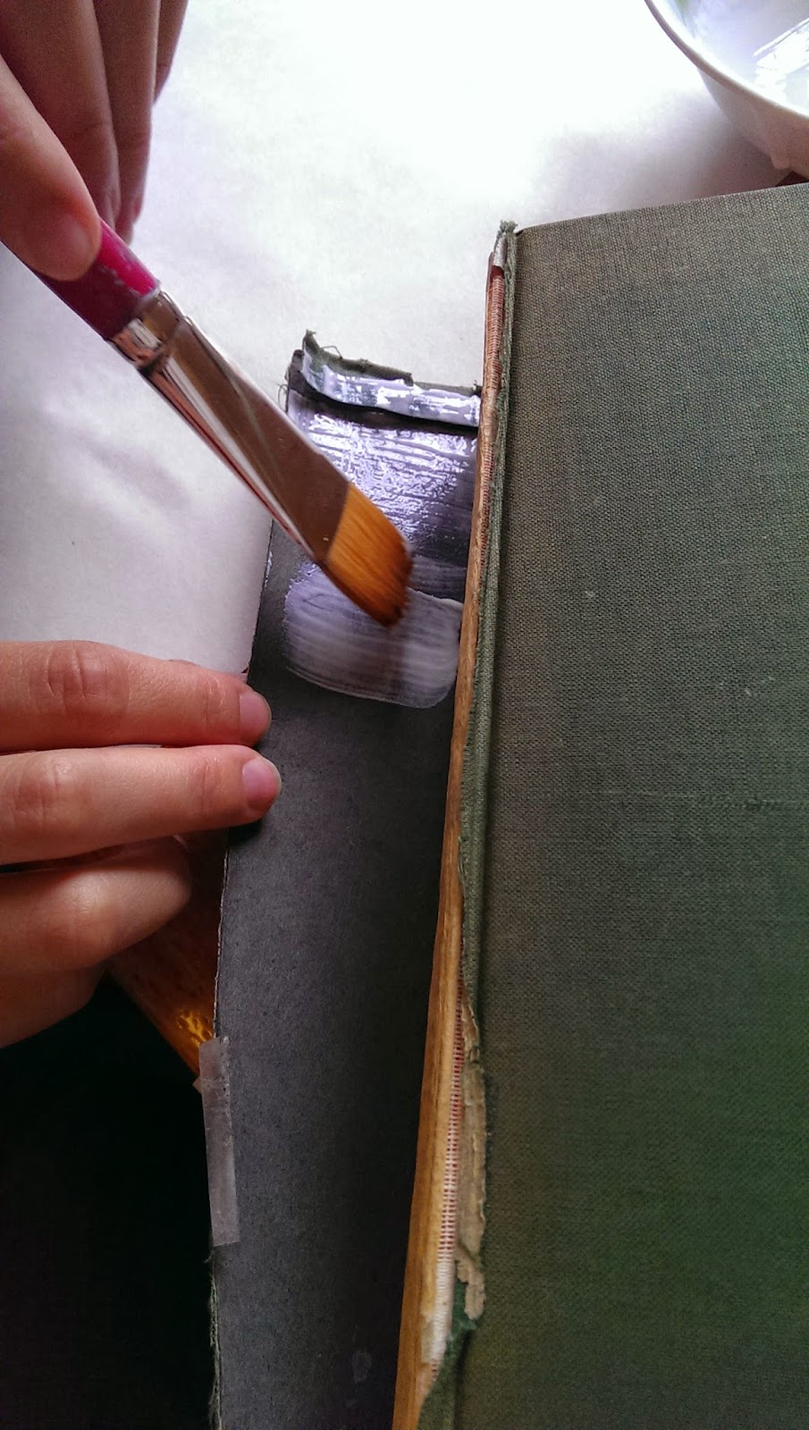 A girl is using a paintbrush to apply white-coloured glue to the spine of an old book that is damaged