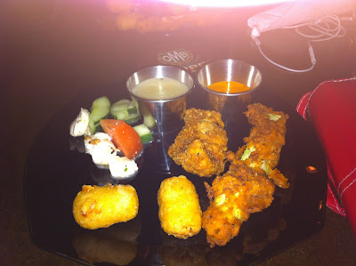 black plate with two mac and cheese bites, a chicken strip, fried zucchini, caprese salad and two dipping sauces.