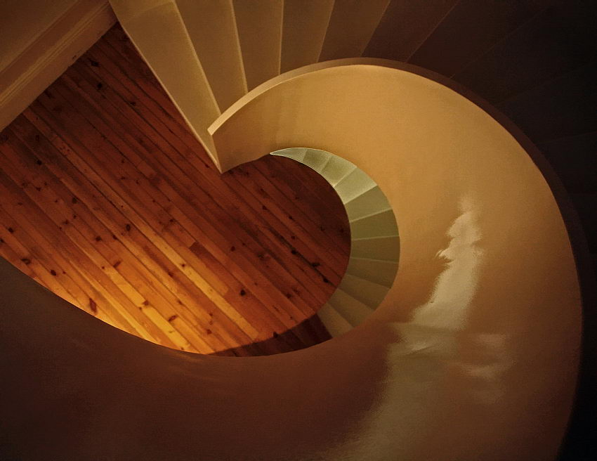 Grafismo duma escada em caracol, vista de cima. Imagem em tons dourados