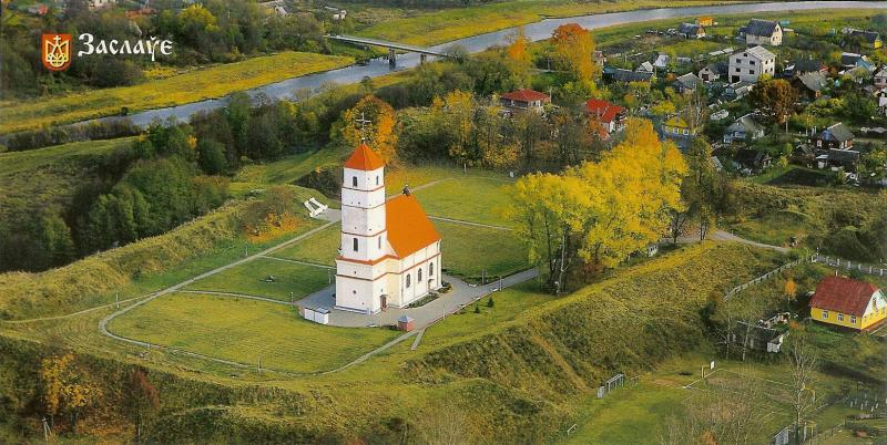 white church with red roof and tower surrounded by grass and trees