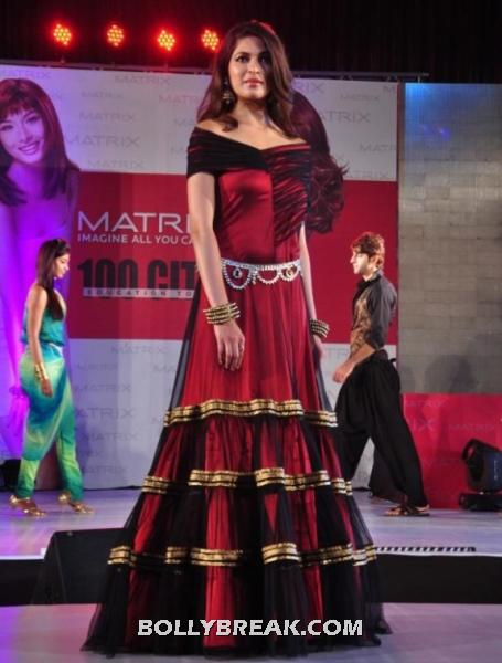 Parvathy omanakuttan poses in a very elegant red and maroon off shoulder gown.  - parvathy omanakuttan in red floor length gown walking the ramp